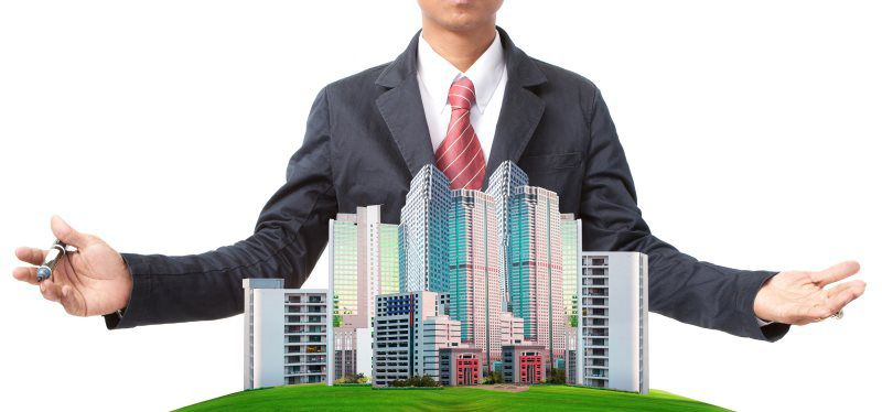 man in a suit with arms open around a miniaturized city skyline standing against a white backdrop